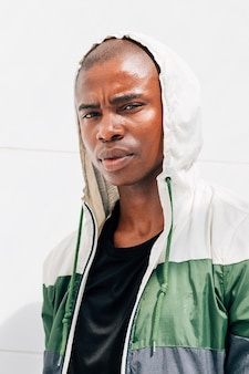 Portrait of a young male athlete in hoodie standing against white wall looking at camera