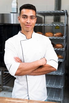 Portrait of a young male baker with his arms crossed looking at camera