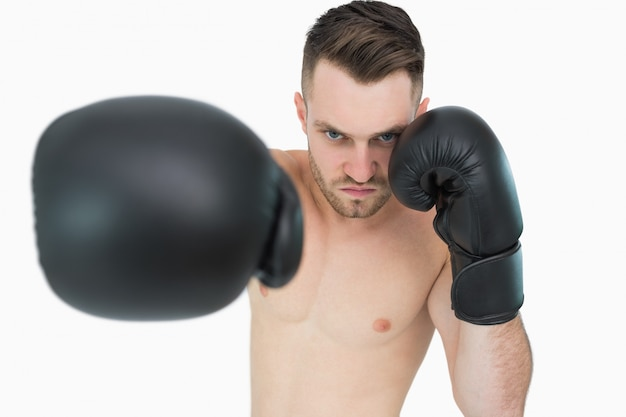 Portrait of young male boxer punching over white background