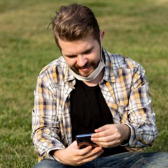 Ritratto di giovane maschio che passa in rassegna il telefono cellulare