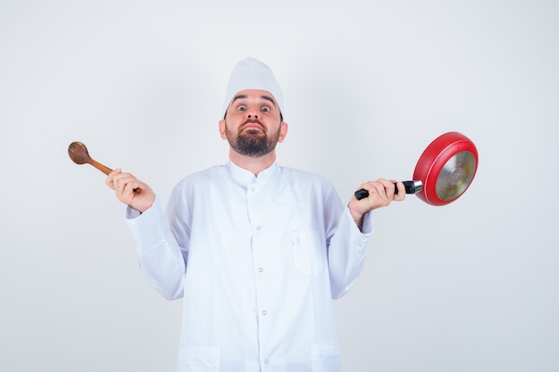 Portrait of young male chef holding frying pan and wooden spoon in white uniform and looking puzzled front view