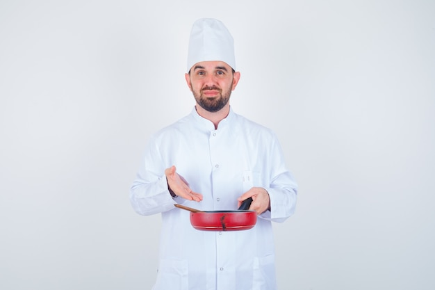 Portrait of young male chef showing empty frying pan with wooden spoon in white uniform and looking downcast front view