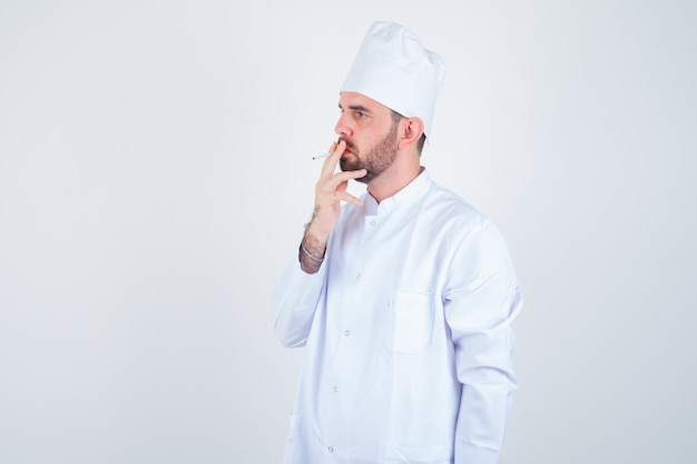 Portrait of young male chef smoking cigarette in white uniform and looking thoughtful front view