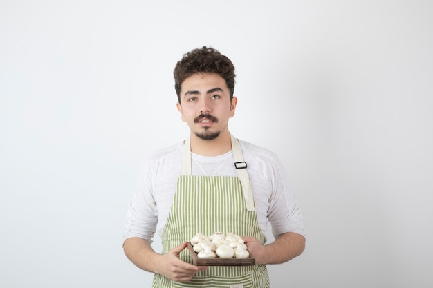 Ritratto di giovane cuoco maschio che tiene i funghi crudi su white