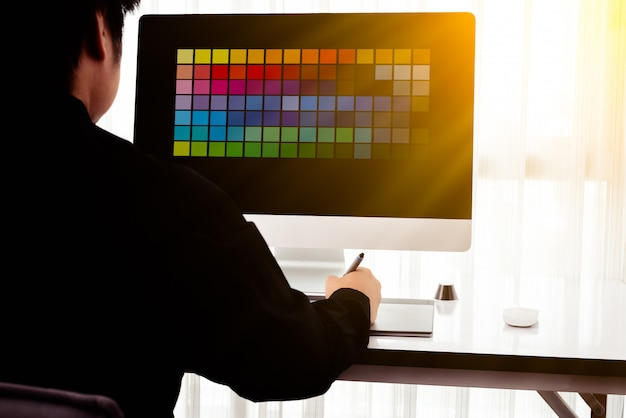 Portrait of young male designer, freelance working with colors at home