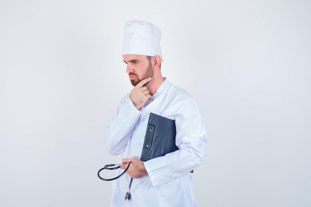 Ritratto di giovane medico maschio che tiene appunti, stetoscopio, toccando la sua barba in uniforme bianca e guardando premurosa vista frontale