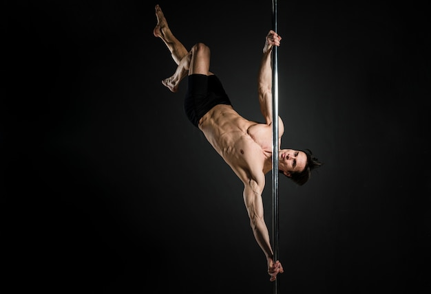 Portrait of young male doing a pole dance