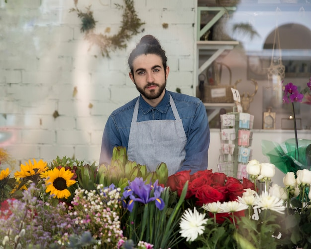 Portrait of a young male florist in apron with beautiful flowers