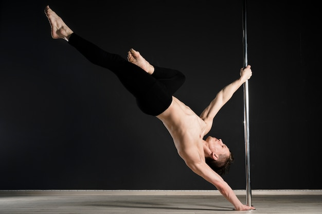 Portrait of young male model performing a pole dance