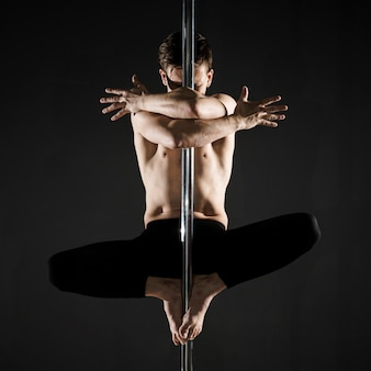 Portrait of young male model pole dancing