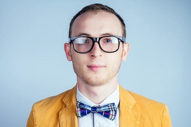 Portrait of a young male nerd in glasses and in a stylish suit