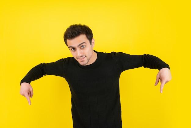 Ritratto di giovane maschio che indica qualcosa sopra il muro giallo