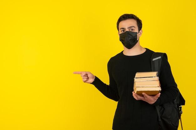 Ritratto di giovane studente maschio in maschera medica che tiene libri del college e indicando