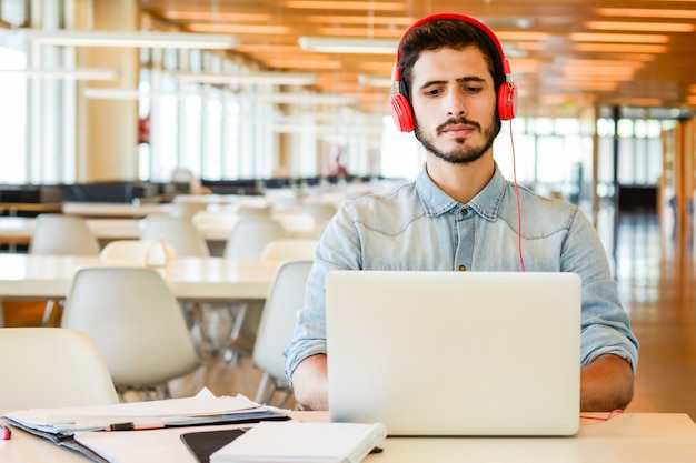 Portrait of young male student using laptop and learning online at the university library. education and lifestyle concept.