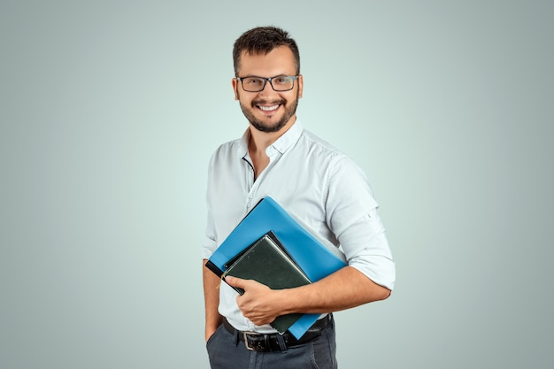 Portrait of a young male teacher on a light background