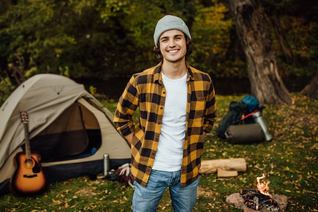 Portrait of young male tourist standing in the forest with tent