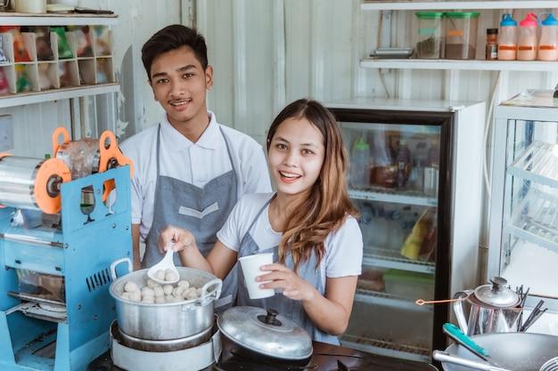 彼女の小さな店で皿ミートボールを販売している肖像画の若い男と女