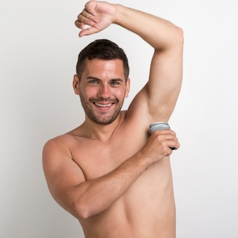 Portrait of young man applying roll on deodorant looking at camera