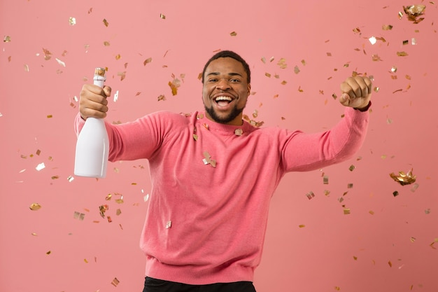 Портрет молодого человека на вечеринке с бутылкой шампанского