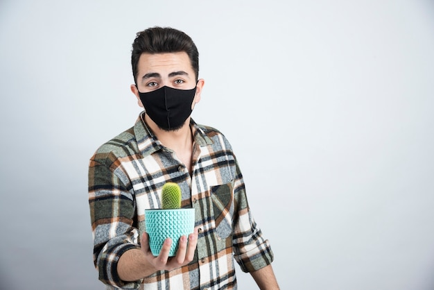 Portrait of young man in black mask holding little cactus in blue pot over white wall.