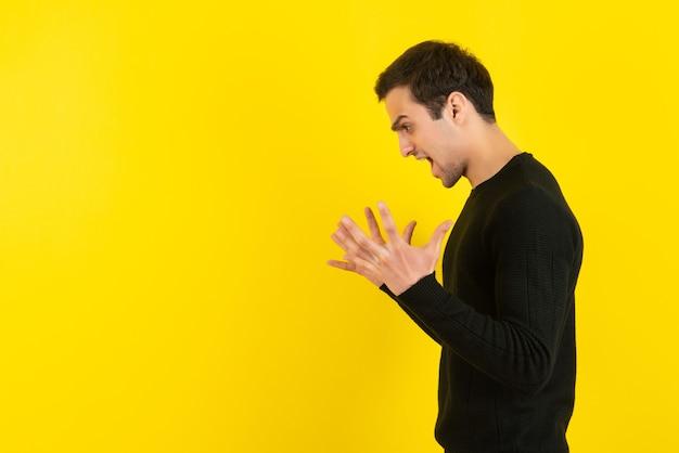 Ritratto di giovane uomo in felpa nera che urla sul muro giallo