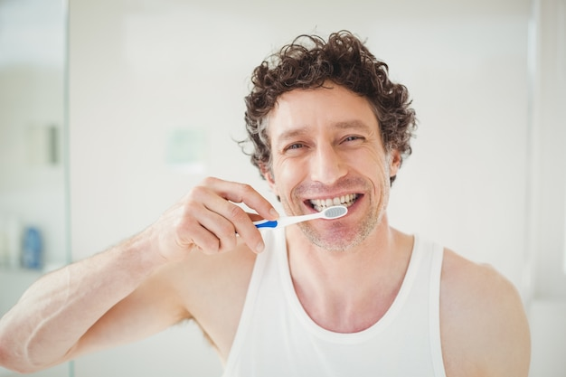 Portrait of young man brushing teeth