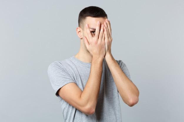 Ritratto di giovane uomo in abiti casual che si nasconde, coprendo il viso con le mani