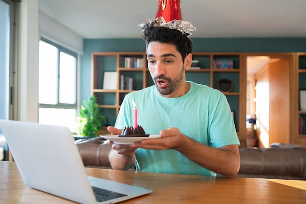 Portrait of young man celebrating birthday on a video call from home with laptop and a cake. new normal lifestyle concept.