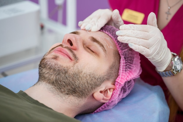 Portrait of young man on cleaning face procedure by woman cosmetologist in beauty clinic. beutician doctor is wiping patient's face with cotton pads. beauty industry concept. guy is lying on couch.