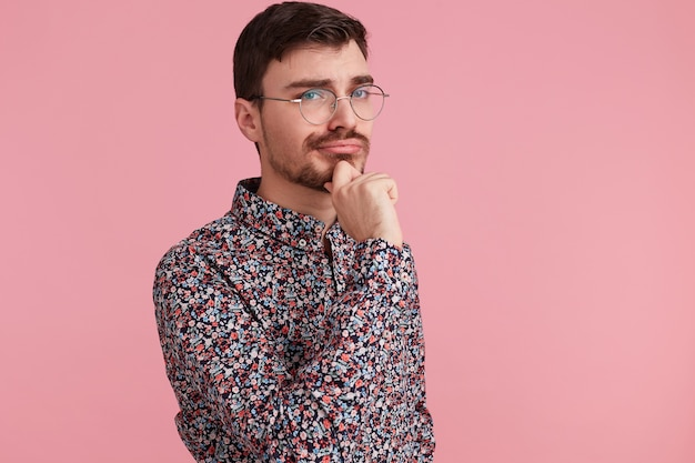 Portrait of young man in colorful shirt looking upwards, copy space on the right side, think about problem, while touches cheek, isolated over pink background.