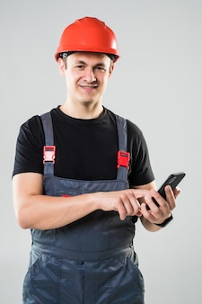 Portrait of young man construction worker with phone wearing protective clothes, helmet and tool belt