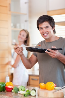 Portrait of a young man cooking while his wife is washing the di