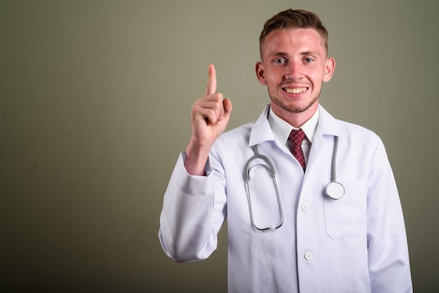 Portrait of young man doctor against colored wall
