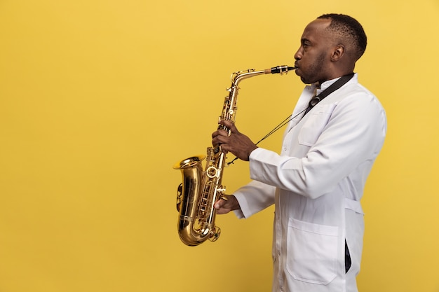 Portrait of young man doctor with saxophone isolated on yellow