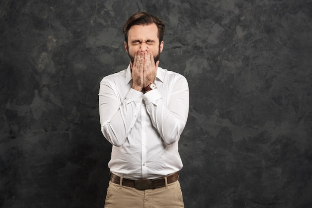 Portrait of a young man dressed white shirt sneezing