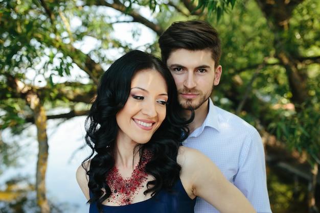 Ritratto di un giovane uomo che abbraccia la sua ragazza da dietro