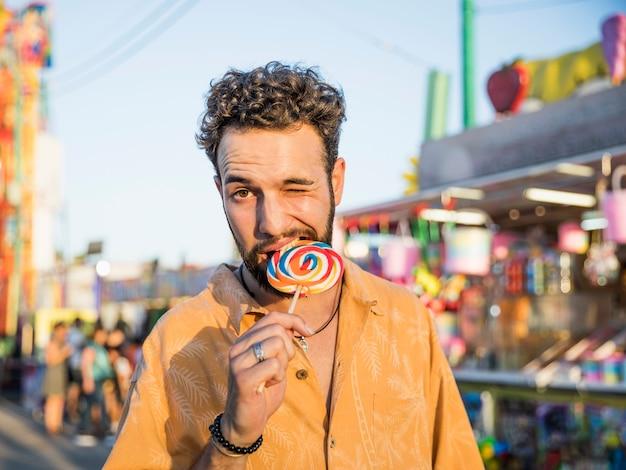 Portrait young man enjoying lollipop
