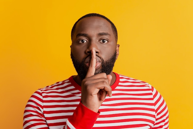 Portrait of young man finger lips show silence sign