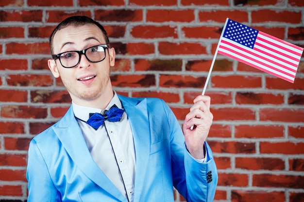 Portrait of a young man (gay) with glasses in a stylish suit and tie holds the flag of america in his hands. concept of gay parades in the usa