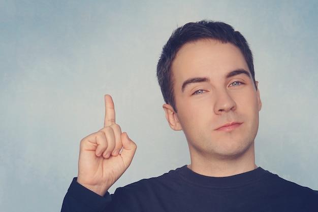 肖像画の若い男は、青い壁の背景に指を上に向けて、アイデアを持っています。思いやりのある人が問題の問題を解決しました。表情、ボディーランゲージ、生命知覚の創造性、