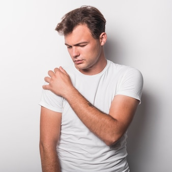 Portrait of young man having pain in shoulder standing against white backdrop