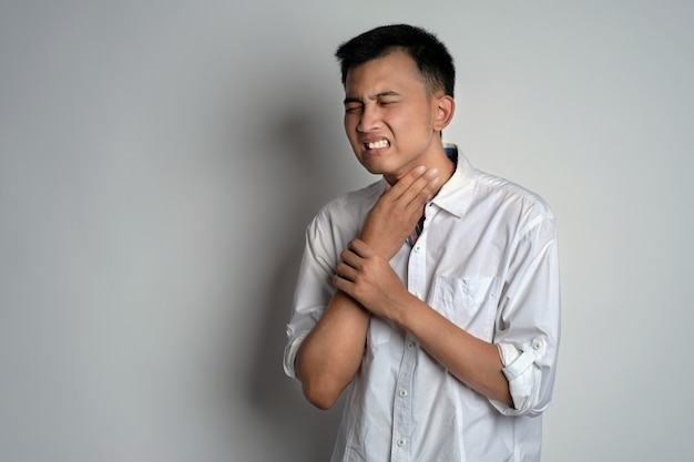 Portrait of young man having sore throat and touching his neck using his hand
