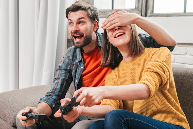 Portrait of a young man hiding his wife's eyes while playing the video game