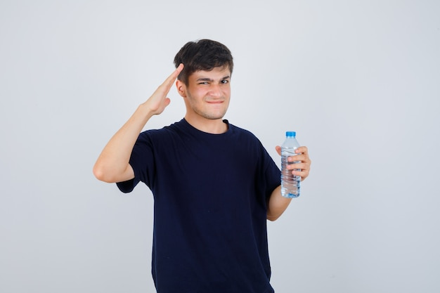 Portrait of young man holding bottle of water, showing salute gesture, pursing lips while frowning in black t-shirt and looking confused front view