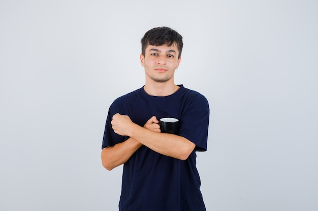 Ritratto di giovane uomo che tiene tazza di tè in maglietta nera e guardando fiducioso vista frontale
