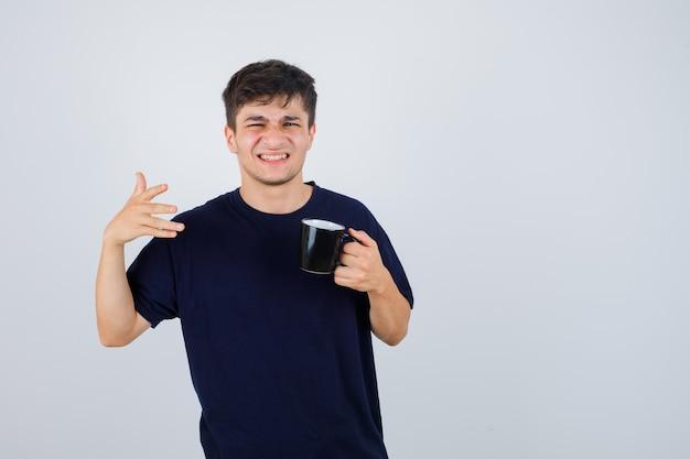 Ritratto di giovane uomo che tiene tazza di tè, indicando lontano in maglietta nera e guardando confuso vista frontale