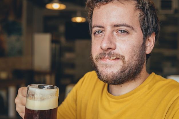 Ritratto di un giovane con in mano un bicchiere di birra fredda