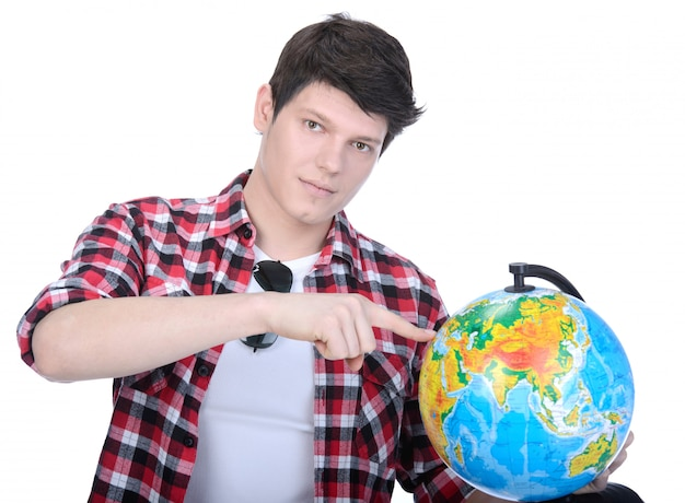 Portrait of a young man holding a globe for travel.