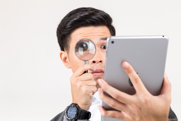 Portrait of a young man holding magnifying glass for reading the tablet.