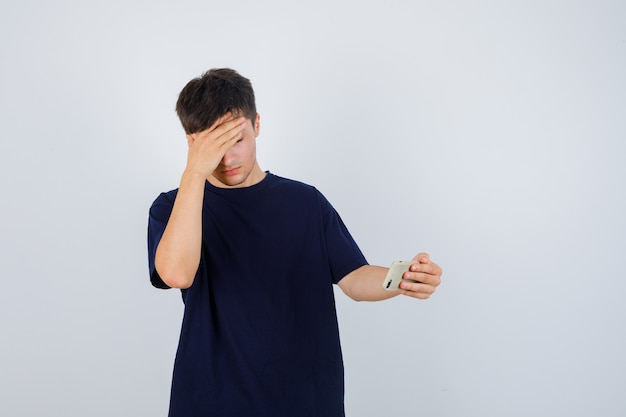 Portrait of young man holding mobile phone, rubbing his forehead in black t-shirt and looking depressed front view